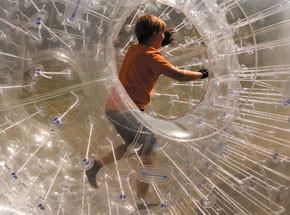 Детский зорбингПодарочные сертификаты<br>Скатиться кубарем со склона внутри упругого мячика. Это зорбинг. Отборный адреналин!<br>Безопасность обеспечат ремни и накачанный в шар воздух. Прозрачный шар совсем не закрывает обзор – небо и земля перемешаются в ваших глазах.<br>